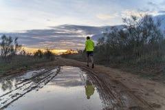 Corriendo en el campo en la puesta del sol en pantalones cortos, con las zapatillas de deporte fotos de archivo