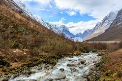 Corriente abajo del río al lago con el backgr de la montaña del casquillo de la nieve Fotografía de archivo