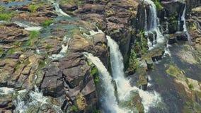 Corriente cercana de las cascadas de la visión aérea de los acantilados escarpados