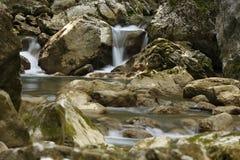 Corriente de la montaña entre las piedras cubiertas de musgo Fotos de archivo