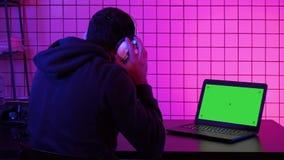 Corriente de observación de las auriculares del videojugador que lleva de un juego Exhibición verde de la maqueta de la pantalla almacen de metraje de vídeo