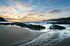 Corriente de ondulación en la playa en la puesta del sol foto de archivo