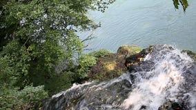 Corriente del agua de la montaña que cae en el río almacen de metraje de vídeo
