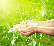 Corriente del agua potable que vierte en las manos del niño Imagenes de archivo
