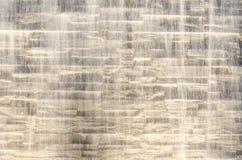 Corriente del agua que cae contra la pared de piedra Imágenes de archivo libres de regalías