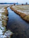 Corriente del agua que fluye en un campo Foto de archivo