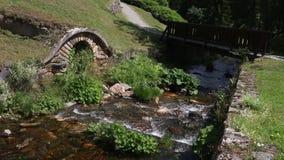 Corriente del agua que fluye entre las paredes de piedra debajo del puente metrajes