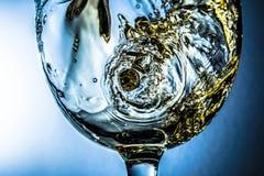 Corriente del vino blanco que vierte en un vidrio, chapoteo del vino blanco en un fondo gris Foto brillante de la visión Foto de archivo