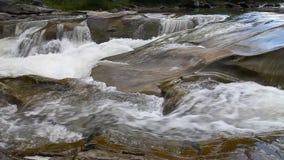 Corriente fuerte de la montaña que fluye sobre rocas metrajes