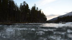 Corriente helada de la cala de la montaña con la acumulación de hielo masiva que fluye en el río almacen de metraje de vídeo
