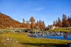 Corriente hermosa en la montaña con el cielo azul, árboles rojos en otoño y puente viejo Foto de archivo