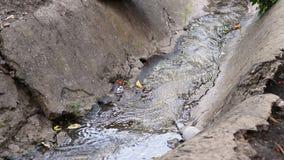 Corriente inútil a la alcantarilla con mala agua de la ciudad, contaminación de agua, dren del agua de aguas residuales de la suc almacen de metraje de vídeo