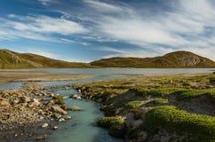 Corriente que fluye del glaciar en un lago El agua es grisácea debido al alto contenido del fango y del légamo de la moraine imágenes de archivo libres de regalías