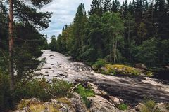 Corriente rápida del río de la montaña del agua en las rocas con el bosque verde en Finlandia fotografía de archivo libre de regalías