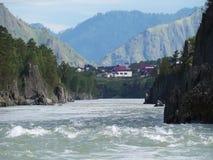Corriente rápida en el río de la montaña con el pequeño pueblo en fondo almacen de metraje de vídeo