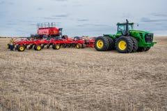 Corriente rápida, SK/Canada- 4 de mayo de 2019: Taladro del granjero, del tractor y de aire que siembra el equipo en Saskatchewan imagen de archivo libre de regalías