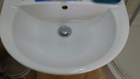 Corrientes en el agujero de dren en fregadero con el torbellino Agua corriente Representación de despilfarro del agua almacen de video