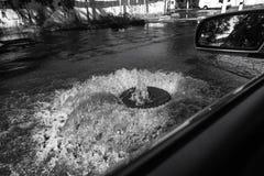 Corrientes fuera de la portilla de las aguas residuales del camino Fuente del drenaje de las aguas residuales Accidente del siste fotos de archivo