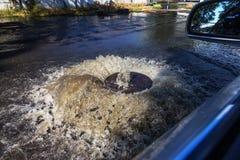 Corrientes fuera de la portilla de las aguas residuales del camino Fuente del drenaje de las aguas residuales Accidente del siste fotografía de archivo libre de regalías