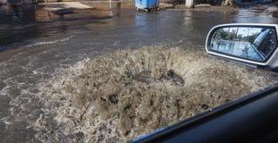 Corrientes fuera de la portilla de las aguas residuales del camino Fuente del drenaje de las aguas residuales Accidente del siste fotografía de archivo