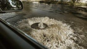 Corrientes fuera de la portilla de las aguas residuales del camino Fuente del drenaje de las aguas residuales Accidente del siste imagenes de archivo