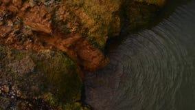 Corrientes minerales en una piedra en un baño del radón Garganta de Karmadon