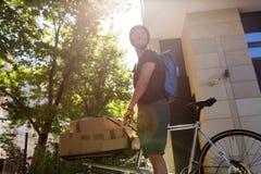 Corriere della bici che effettua una consegna fotografie stock