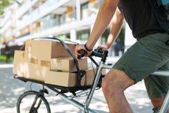 Corriere della bici che effettua una consegna fotografia stock