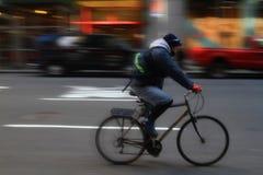 Corriere di NYC che va in bicicletta su una via della città di Manhattan Immagini Stock