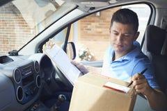 Corriere In Van With Clipboard Delivering Package a Hou domestico immagini stock libere da diritti