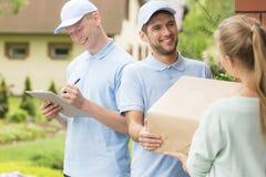 Corrieri in uniformi blu e cappucci che danno pacchetto ad un cliente immagini stock