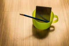 Corrigez et carnet dans une tasse de l'eau verte photo libre de droits