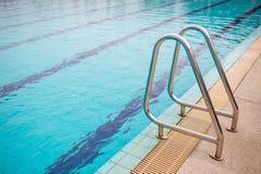 Corrimani inossidabili della scala per la discesa nella piscina Piscina con il corrimano immagini stock libere da diritti