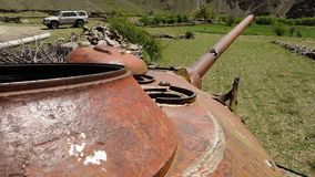 Corroded, old war tank. A hand held, long shot of a corroded, rusty top of a war tank and an automobile parked in the vicinity of it stock video