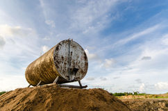 Corroded and rusty oil storage barrel against beautiful blue ski Royalty Free Stock Photos