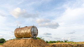 Corroded and rusty oil storage barrel against beautiful blue ski Stock Photo