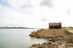 Corroded and rusty oil storage barrel by the water against beaut Royalty Free Stock Photo