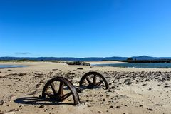 Corroded and stranded wheels on beach / coast. Corroded and stranded metal wheel axle stuck in sand close to the coast royalty free stock image