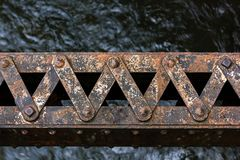 Corroded support over water. Corroded rusted metal support over a dark blue river Stock Images