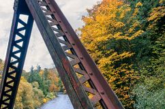 Corroded supports in autum. Corroded rusty metal supports in autumn above a river on a cloudy day Stock Photo