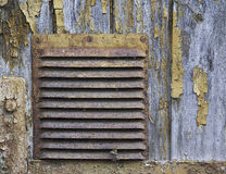 Corroded ventilation hatch on the wooden background with peeled of paint Stock Photography