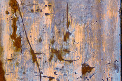 Corroded weathered metal background texture. With remnants of colored paint in pink and blue with rusty scratches and a pitted surface Royalty Free Stock Photography