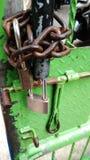 Corrosive chain and padlock at iron green gate. Photo corrosive chain and padlock at iron green gate royalty free stock photo