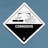 Corrosive hazard symbol warning sign on blue. Corrosive, destroys living tissue on contact, hazard symbol or warning sign on a painted wall warning not to expose Royalty Free Stock Image