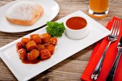 Corroyez la saucisse épicée de wurst avec le cari et le ketchup photos stock