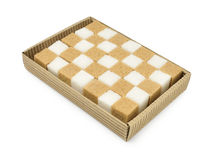 Corrugated box with brown and white sugar cubes isolated on white. Corrugated carton box with brown and white sugar cubes Stock Images