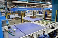 Corrugated cardboard production line. View of corrugated cardboard production line at the plant stock images