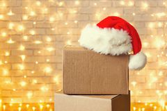 Corrugated fiberboard boxes with christmas lights on background. Stack of four blank brown freight boxes, different size, brick wall with Christmas lights on stock photography