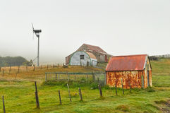 Corrugated iron farm outbuildings and wind turbine Stock Photos