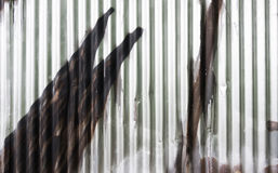 Texture of fence from corrugated iron with graffiti detail. Silvery wall from a wavy metal sheet sprayed with brown color. Close-up of pop art in urban street royalty free stock images